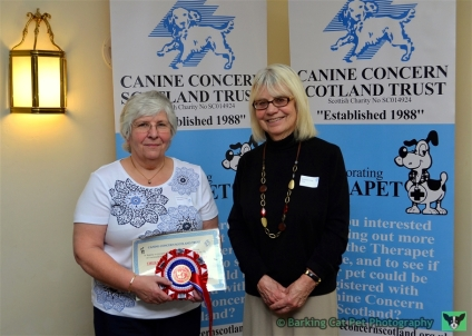 Area Representative Linda Macdonald accepts the 20 Years' Service Award on Behalf of Fiona Stalker & Poppy from Patron Rosemary Long